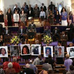 In this photo taken June 19, 2015, photos of the victims of the shooting at Emanuel AME Church in Charleston, S.C., are held during a vigil at the Metropolitan African Methodist Episcopal Church in Washington.